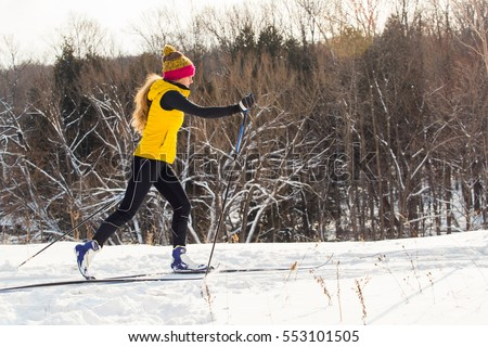 A young woman cross country skiing in Ontario, Canada.  #553101505