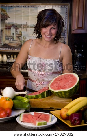 A young woman cutting watermellon in the kitchen
