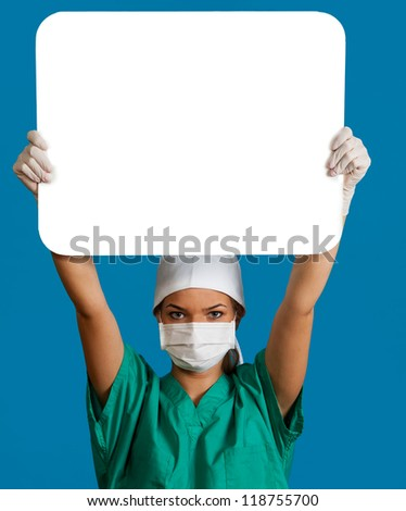 A young woman doctor in a mask holding an empty bill board over her head against a blue background.