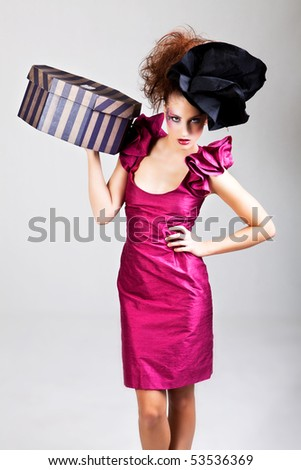 A young woman dressed in avant garde attire and carrying a hat box. She is wearing a hat and has cosmetic artwork on her right temple. Vertical shot.