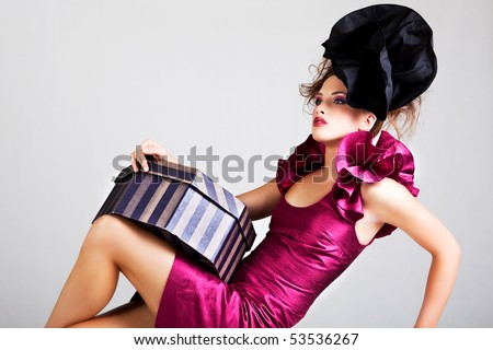 A young woman dressed in avant garde attire and holding a hat box. She is wearing a hat and has cosmetic artwork on her right temple. Horizontal shot.