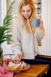 a young woman drinks hot cocoa sitting on the kitchen table. Christmas pastries. Pleasant New Year's chores.
