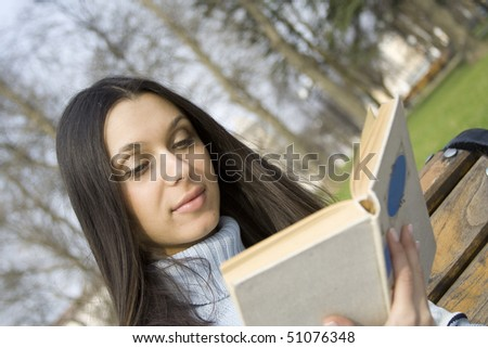 A young woman during the day in the park sits on a bench holding a book and read it