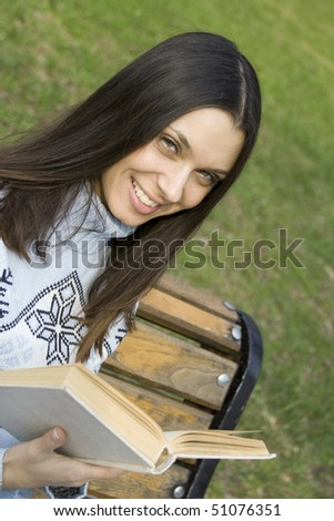 A young woman during the day in the park sits on a bench holding a book. He smiles and looks into the frame