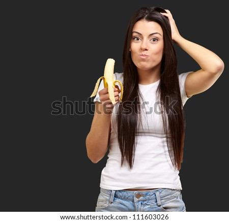 A Young Woman Eating A Banana On Black Background
