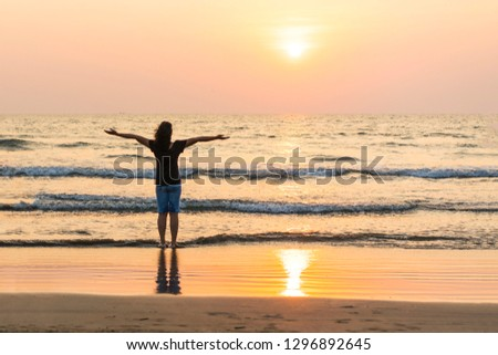 A young woman enjoying the beautiful pink sunset on the beach near to the ocean. #1296892645