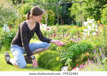 A young woman enjoys the flowers in the garden - stock photo