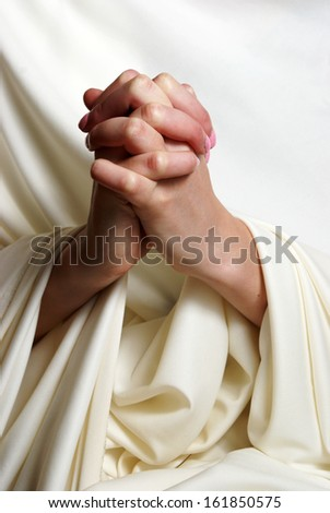 A young woman faithfully brings her hands together in essence of prayer.