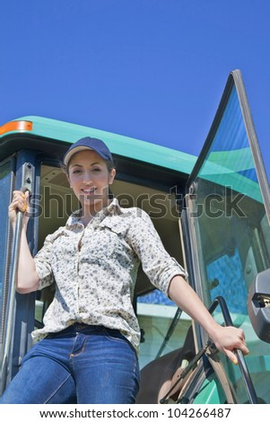 A young woman farmer stepping out of the cab of her tractor.