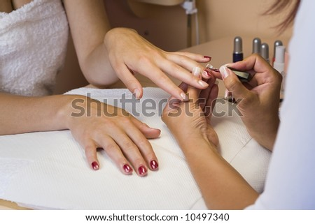 A young woman getting her nails painted during a manicure