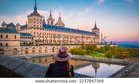 A young woman, girl with hat during beautiful sunset with the reflection in a water pond at Frailes Garden at San Lorenzo de El Escorial monastery during fall time near Madrid, Spanish capital.