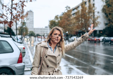 A young woman hailing a taxi in the rain.