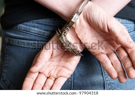 A young woman has been arrested and handcuffed behind her back.