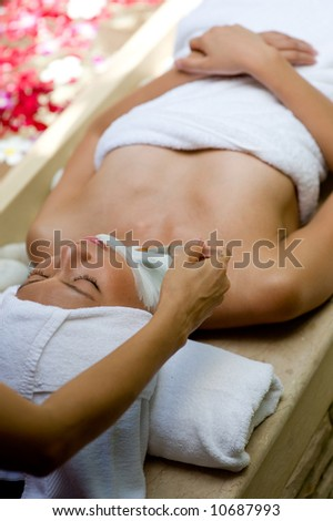 A young woman having facial treatment at a spa