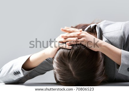 A young woman hiding her face on table