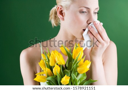 A young woman holding a bunch of tulips, blowing her nose