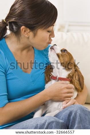 A young woman holding a dog on her lap and making a kissing gesture. She has dark brown hair. Vertically framed photo.