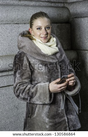 A young woman holding a mobile phone is looking at you./Portrait of Young Woman