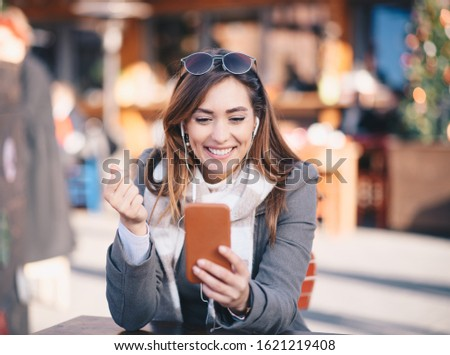 A young woman holding a phone and wearing headphones at a cafe. She also wears stylish clothes and sunglasses.