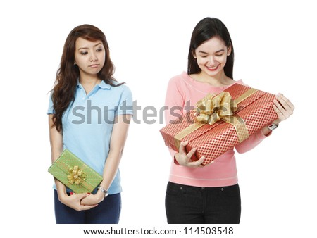 A young woman holding a small gift, envious of the much bigger present of a friend (on white background)