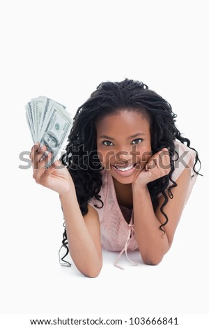 A young woman holding American dollars is resting her head on her hand against a white background