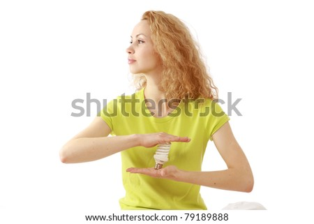A young woman holding an energy-saving bulb between her hands, isolated on white