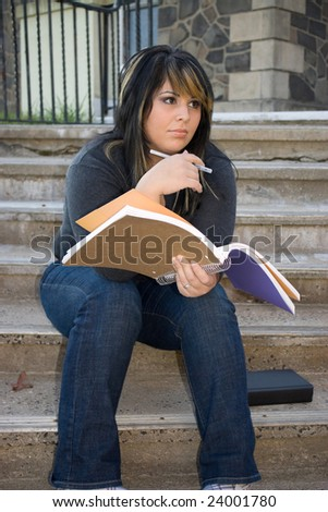 A young woman holding her notebook while sitting on the campus stairs.