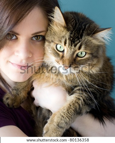 A young woman holding her pet Maine Coon cat.