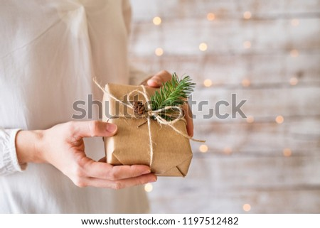 A young woman holding wrapped Christmas present.