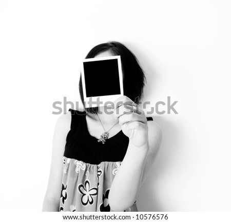 a young woman holds a instant photo in front of her face