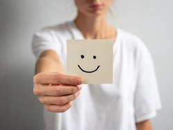 a young woman holds a paper sticker with a drawn smiley face in her outstretched hand. Focus on the hand and sticker, blurred background
