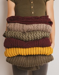A young woman holds a stack of warm clothes in autumn colors. Sweaters in yellow, dark green, brown