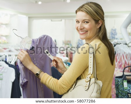 A young woman holds onto the price tag of a blouse while shopping.  She is smiling over her shoulder towards the camera.  Horizontal shot.