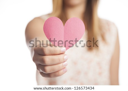 A young woman holds out a cut out construction paper heart.