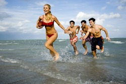 A young woman in a bikini being chased by three men