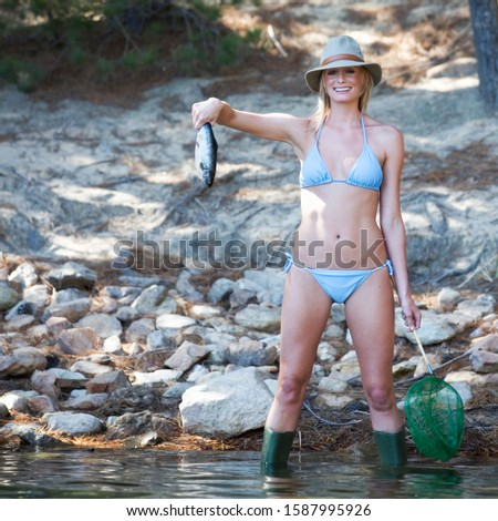A young woman in a bikini holding a fish