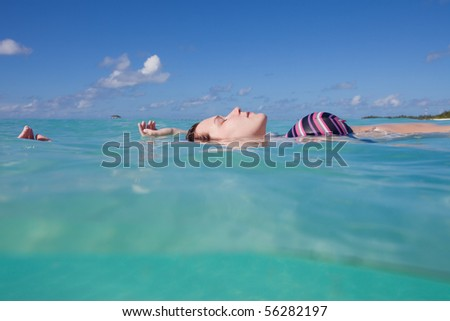 A young woman in a bikini lying upon the water surface with her eyes closed - stock photo