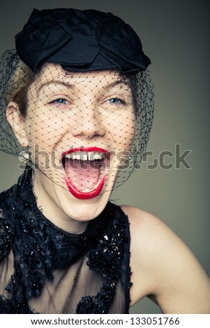 A young woman in a black outfit laughing