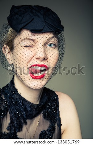 A young woman in a black with her tongue out in a cheeky expression