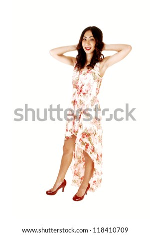 A young woman in a evening dress standing for white background with her hands behind her head, with long brunette hair.