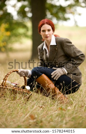 A young woman in a field holding a wicker basket