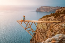 A young woman in a green dress sits on the edge of a wooden bridge at a height in the mountains above the sea and enjoys the view of the coast. The concept of travel and active recreation