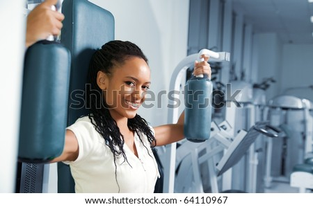 A young woman in a gym with a confident smile