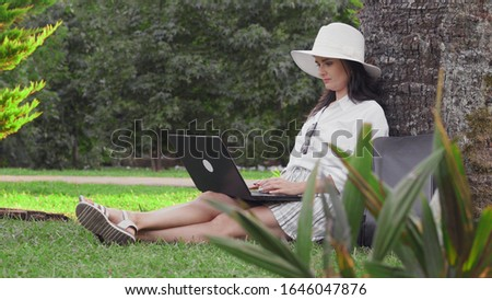 A young woman in a hat sits and works behind a laptop in a park sitting on the grass.