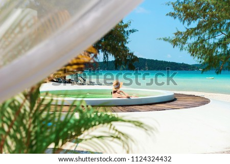 A young woman in a jacuzzi admires a beautiful view of the sea and a white sandy beach, Cambodia, Ko Rong Island.A girl rests in a jacuzzi in the fresh air against the turquoise sea. #1124324432