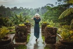 A young woman in a long dress and wearing a hat is standing with her back against the background of a green tropical jungle, Ubud Bali. Romantic girl walks around the grounds of a luxury hotel in Ubud