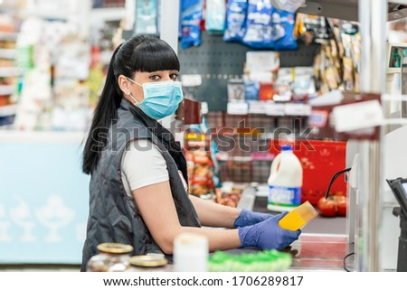 A young woman in a medical mask and gloves, working at the checkout in a supermarket. Concept of coronovirus, protection from infection and industrial crisis