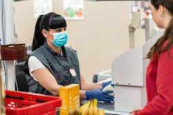 A young woman in a medical mask and gloves, working at the checkout in a supermarket. In the foreground is a customer in a blur. Close up. Concept of coronovirus and protection from infection