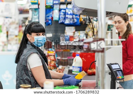 A young woman in a medical mask and gloves, working at the checkout in a supermarket. In the background, the buyer is blurred. Concept of coronovirus, protection from infection and industrial crisis