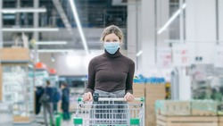 A young woman in a medical mask stands in a supermarket with a food cart in a crowd of people, timelapse. Protection from coronavirus, the purchase of food for the quarantine. Defecit of products.